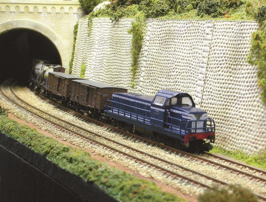 Un train de marchandises émerge d'un tunnel donnant accès à l'une des courbes menant à la coulisse située à l'arrière du réseau.