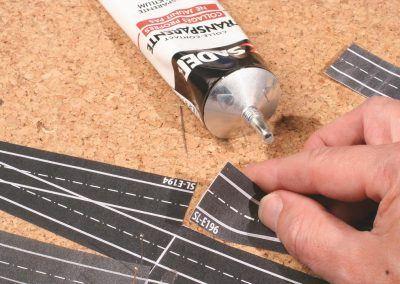 12-Tenue à l'autre extrémité par des épingles, celle-là est délicatement soulevée et le liège est encollé, puis pressé.