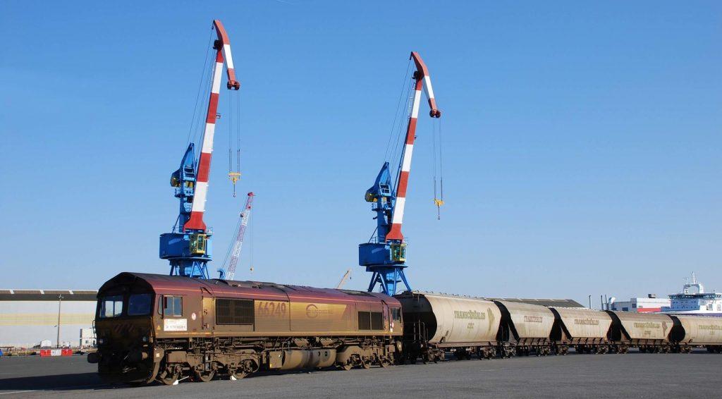 L'ambiance portuaire est plantée avec, en arrière-plan, les cargos et grues du port de Saint Nazaire. La Class66 louée par l'OFP OuestRail, créé par le groupe Millet, dessert l'embranchement Cargill plusieurs fois par semaine.