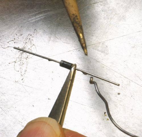 3 - Étamage de queues de composants avec des brucelles en protection thermique.
