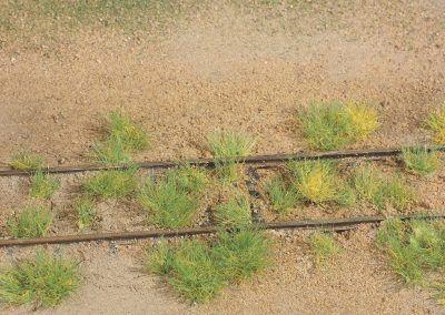 13–Les touffes sont disposées aléatoirement de part et d'autre des rails. Aidez-vous de la photo réelle ci-dessus.