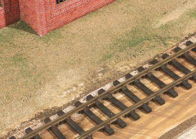 3–La voie a pris sa place par collage à la Néoprène. Notez que la plate-forme a été peinte rapidement avant de recevoir le ballast et le sable par la suite.
