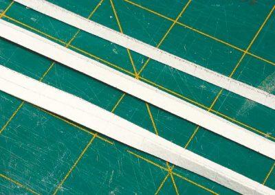 21-Les bandes de papier sont pliées à 90° pour former les côtés de la bordure.