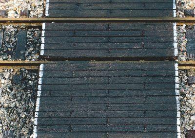 28-Les planches ont reçu une terre à décor noire appliquée à sec qui imite la créosote, produit qui protège le bois du pourrissement. A noter, la peinture en blanc des bords du passage imitant comme dans la réalité les bandes de visibilité.