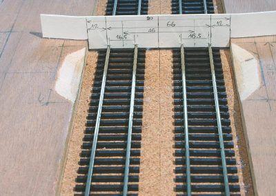 8-Les deux voies Roco (code 83) sont posées ici par collage à la Néoprène et contrôlées par un gabarit réalisé en carton dur.