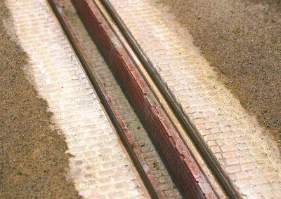 10 – Une peinture puis un saupoudrage de sable coloré sont appliqués de part et d'autre du pavage. Si c'est une fosse de visite dans un dépôt vapeur, le sol et la fosse sont noircis très fortement.