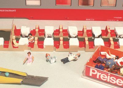 Nous allons maintenant installer des voyageurs à nos tables. Notre choix se fera parmi les personnages assis de la gamme Preiser. Leur mise en place nécessitera quelques «amputations».