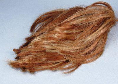 La perruque d'un mélange de blond et d'auburn probablement, convient bien pour l'utilisation prévue. Ses fibres viendront casser la monotonie de la hauteur des autres fibres plus courtes et varier la couleur avec des tonalités plus roussies.