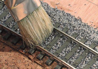 11-La brosse tenue faiblement penchée avec légèreté permettra un balayage propre du dessus des traverses et minimisera la quantité de cailloux sur ces dernières.