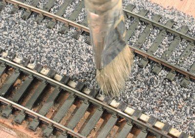 12-La partie centrale entre les deux voies est travaillée de la même façon que les voies. Une fine couche est balayée puis tapotée pour bien répartir le ballast. A gauche la partie mise en forme.