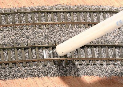 18-La colle est délicatement appliquée sur le ballast en commençant par le milieu de voie.