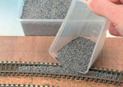 9-Nous avons préféré un mélange de deux ballasts à la couleur opposée plutôt que de poser un granulé monocouleur : affaire de goût. La mesurette à lessive est bien pratique pour déposer le ballast sur la voie.